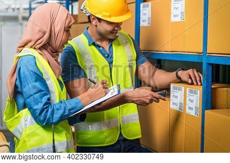 Asian Idian Worker Man With Muslim Worker Woman Working Together By Scanning Bar Code And Qr Code In