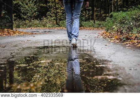 Reflection Of Girl Wearing White Shoes In Water Puddle. Unknown Woman Passed Small Puddle. Reflectio