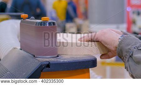 Professional Man Carpenter Hands Using Belt Sander Machine, Polishing Wood Product At Workshop - Clo