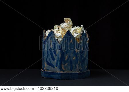 Cardboard Crown On A Black Background. Paper Product. Fake Crown Filled With Crumpled Paper. A Slopp