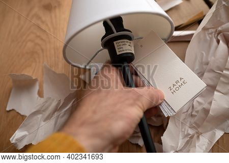 Paris, France - Dec 13, 2020: Pov Male Hand Holding Paper Tag Of A Zara Home Table Elegant Lamp With