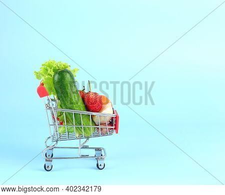 Red Shopping Cart Filled With Various Vegetables And Fruits