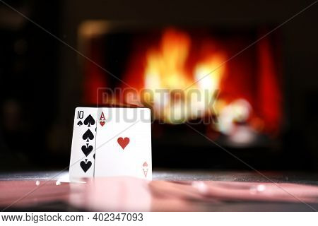 Poker Cards On A Table Against The Background Of A Fireplace. Online Gambling. Gamble Addiction.