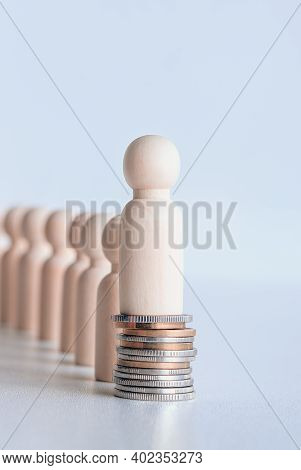 Miniature Wooden Figures Of People Standing On Stack Of Coins. Inequality And Social Class. Income A