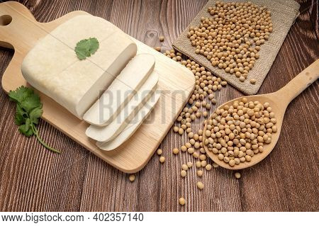 Fresh Tofu And Sliced Tofu On Wood Cutting Board With Soy Bean In Wooden Spoon. Full Depth Of Field.