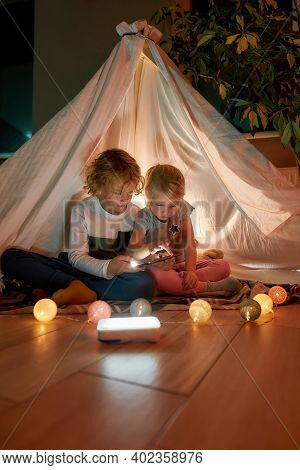 Two Little Kids, Brother And Sister Using Tablet Pc While Sitting On A Blanket In A Teepee Made With