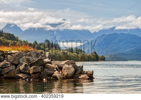 Fjord Landscape Norway. Stone Fjord Shore And Mountain Peaks Behind Low Clouds