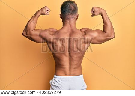 Back view of bodybuilder man, posing showing back muscle