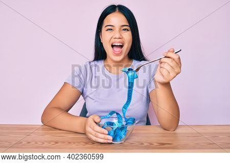 Young asian girl eating measure meter doing diet for weight loss celebrating crazy and amazed for success with open eyes screaming excited.