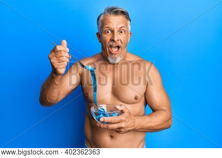 Middle age grey-haired man shirtless eating measure meter doing diet for weight loss celebrating crazy and amazed for success with open eyes screaming excited.