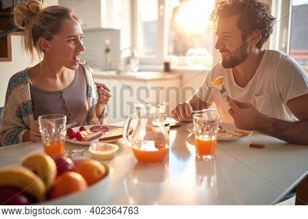 A young couple in love eating breakfast at home on a beautiful sunny morning. Relationship, love, together, breakfast