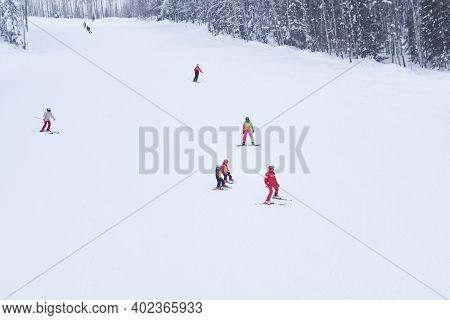 Perm Krai, Russia - January 02, 2021: Amateur Downhill Skiers Ride On A Forest Ski Track