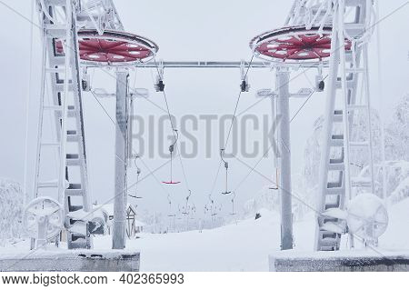 Upper Tower Of The Ski Lift On A Snow-covered Hilltop Among Frosty Trees