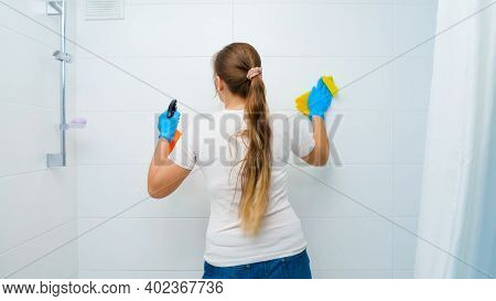 Young Housewife Doing Domestic Chores And Washing Walls In Bathroom. Having Good Time And Fun At Hou