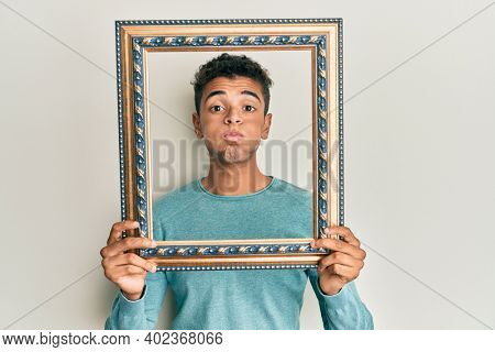 Young handsome african american man holding blank empty banner puffing cheeks with funny face. mouth inflated with air, catching air.