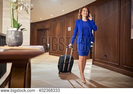 Happy businesswoman entering hotel on her trip, with her suitcase