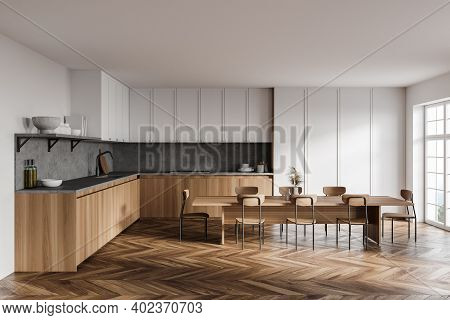 Interior Of Modern Kitchen With White Walls, Wooden Floor, Wooden And White Cupboards And Long Dinin
