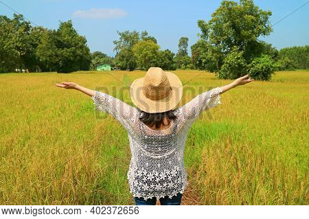 Happy Female Farmer Raising Her Arms In The Paddy Fields Ready For Harvesting