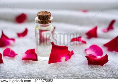 Rose Oil In Glass Bottel With Red Rose Petals On White Towel  Background. Aroma Therapy Spa And Mass
