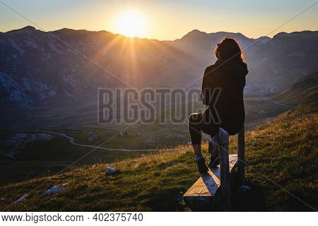 Woman in nature in sunset. People in nature. Beautiful woman relaxing in nature in sunset. Beautiful people. Happy people. Happy beautiful woman in nature in sunset. Woman sitting on bench in sunset. Woman. People. Sunset. Nature.