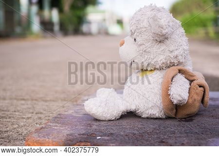 Broken Heart Concept. Alone Teddy Bear Sitting On Road. Conveys A Lonely Mood, Chagrin, Lovelorn.
