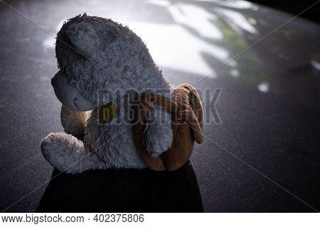 Broken Heart Concept. Alone Teddy Bear Sitting On Black Dark Floor. Conveys A Lonely Mood, Chagrin,