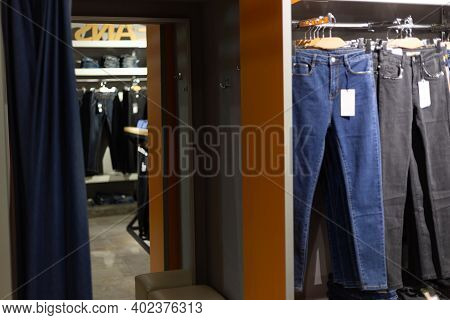 Row Of Hanged Blue And Black Jeans In A Shop.