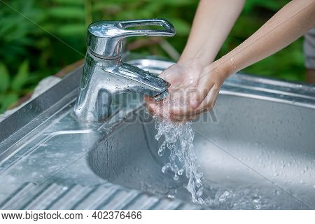 Baby Try To Turn Off Water Faucet But Water Still Leak. A Child's Hand Turning Off The Tap. Save Wat