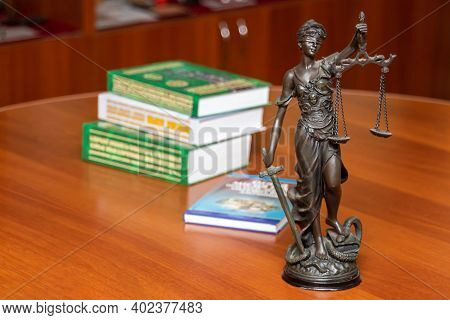 Statue Of Blindfolded Themis With A Sword And Scales In Her Hands, Standing On A Desk With Books On
