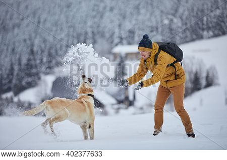 Young Man With Dog In Winter. Pet Owner With His Labrador Retriever Playing In Snow Against Old Vill