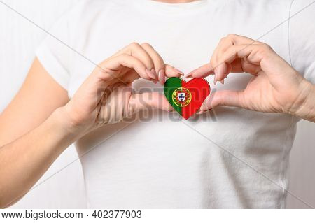 Love Portugal. The Girl Holds A Heart In The Form Of The Flag Of Portugal On Her Chest. Portuguese P