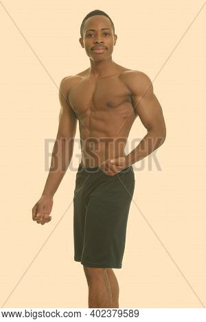 Young Handsome African Man Shirtless Flexing Left Arm