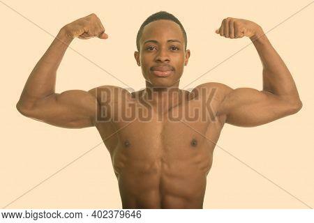 Young African Man Shirtless Flexing Both Arms
