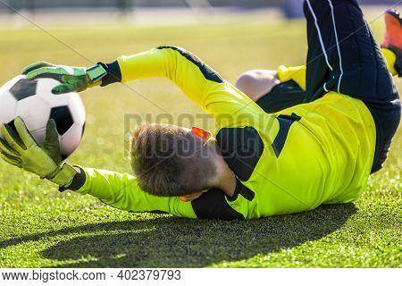 Soccer Goalie Catching Ball. Young Boy Goalkkeeper Saving Goal. Acrobatic Football Goalkeeper Save.