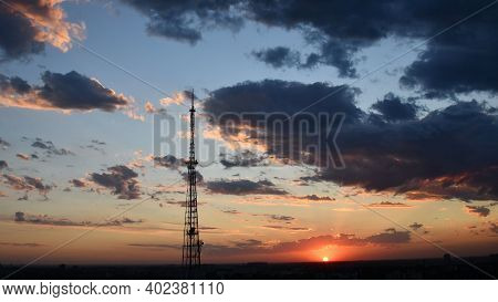 Cloudscape With Industrial Communication Tower And Dark Purple Clouds While Golden Sunbeams Shining