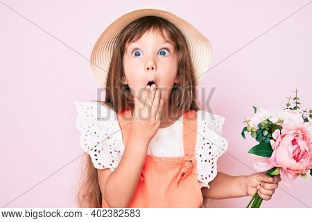 Little caucasian kid girl with long hair holding flower wearing spring hat covering mouth with hand, shocked and afraid for mistake. surprised expression