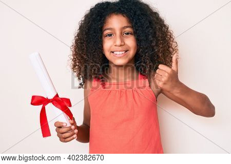 African american child with curly hair holding graduate degree diploma smiling happy and positive, thumb up doing excellent and approval sign