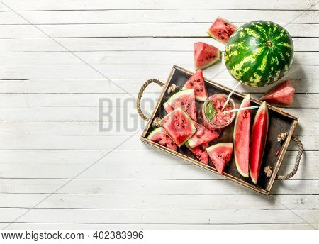 Watermelon Juice In Glass Jar On A Tray With Slices Of Watermelon. On A White Wooden Table.
