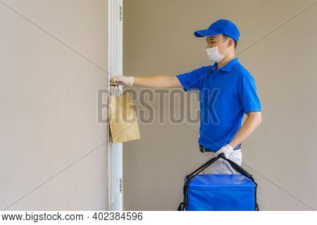 Asian Delivery Man Send Food Bag At Door Knob For Contactless Or Contact Free From Delivery Rider In