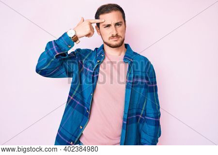 Young handsome man wearing casual clothes pointing unhappy to pimple on forehead, ugly infection of blackhead. acne and skin problem