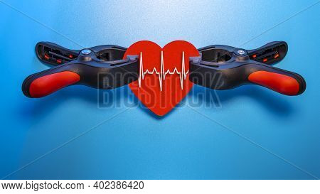 Healthcare And Medicine Concept - Close Up Of A Red Heart With An Ecg Line Clamped In A Vise For Res