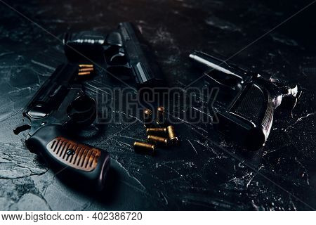 Group Of Pistols And Bullets On Black Concrete Table. 9mm Handgun. Vintage Revolver With A Drum. Sev