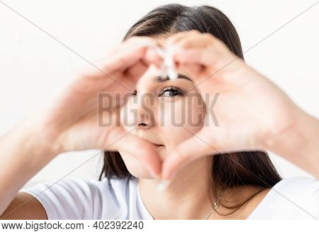 Young Happy Brunette Woman In White T-shirt Showing Heart Sign With Her Hands In Front Of Face