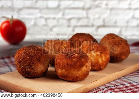 Delicious Hot Italian Arancini - Rice Balls Stuffed With Cheese On A Board On An Old Wooden Table