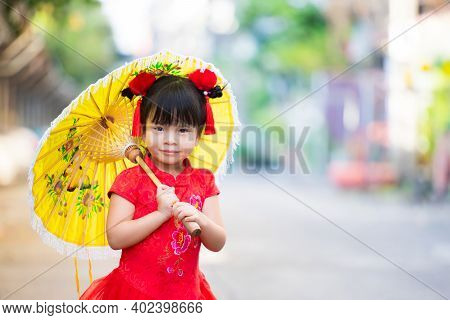 Chinese New Year Happiness Concept. Cute Girl Wearing Red Qipao Dress Walks In Yellow Vintage Umbrel