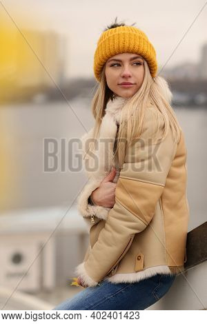Girl In Knitted Yellow Hat And Coat Close Up Portrait On City Architecture Background