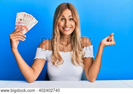 Beautiful blonde young woman holding 10 colombian pesos banknotes screaming proud, celebrating victory and success very excited with raised arm