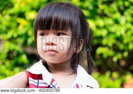 Close Up Of Little Child Face Is Looking At Something Wondering From Her Side. Cute Girl Cut The Ban