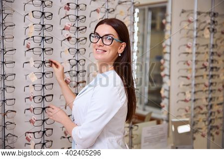 Optician Standing Near The Stand With Glasses
