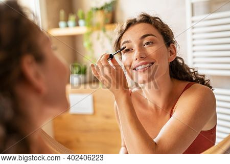 Beautiful woman using mascara on eyelash in bathroom in the morning time. Smiling young woman applying eye make up and looking at mirror. Beauty girl applying black mascara in bathroom at home.